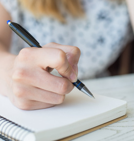 Woman writing on notepad, creating with confidence